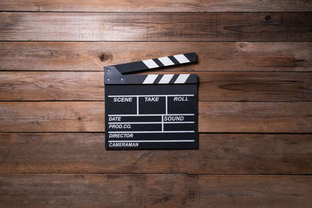 movie clapper on wood table ; film, cinema and video photography concept, flat lay