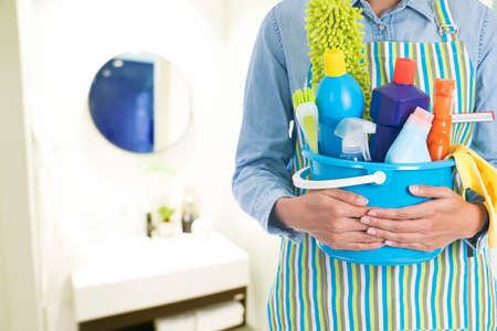 woman with cleaning equipment ready to clean house on bathroom blur background Standard-Bild