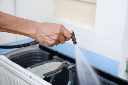 Engineer or repairman fixing and cleaning air conditioner unit by high pressure water jet