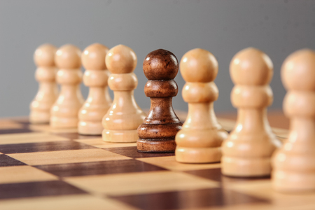 A black pawn stands in the middle of a row of white pawns, either remarking its different characteristics of the groups acceptance.