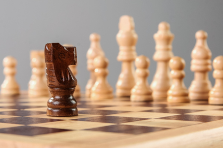 Black wooden chess kinght challenges white side alone. Courage against challenging circumstances. Banco de Imagens