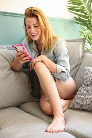 Blonde young woman sits on her legs on a lounge