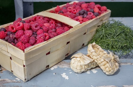 bast: Raspberries in a basket on a bench with bast shoes Stock Photo