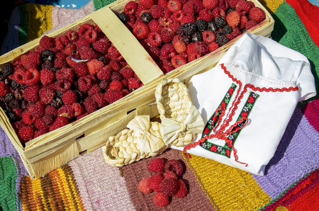 Raspberries in a basket on a bench with bast shoes and embroidery Stock Photo