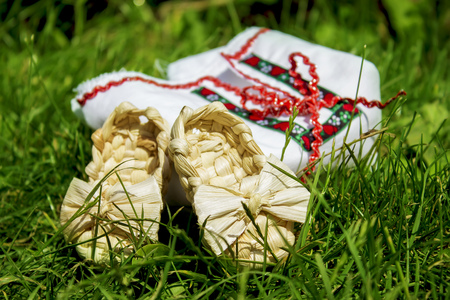 Beautifull embroidery with bast shoes in grass Stock Photo