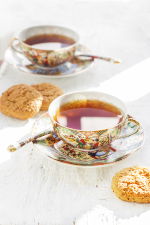 Two Japans cups of tea with spoons and cookie on the white background Stock Photo
