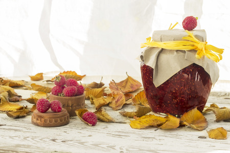 Autumn red and yellow leaves with raspberry jam on the wooden background