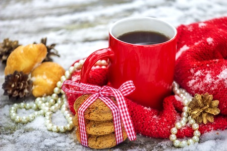 Red cup of tea, and oat cookies on the old wooden table in winter on Christmas Stock Photo