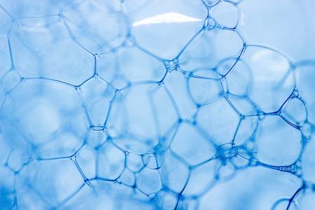 매크로보기 흰색 비누 거품 거품. 비눗물과 샤워 텍스처. 파란색 배경입니다. 수평, 소프트 포커스