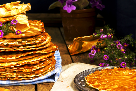european food: Pile of rustic homemade wafers with paper, flowers and waffle-iron on the old wooden background. Russian food. East european food