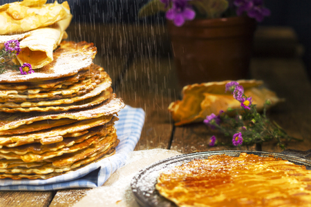 european food: Pile of rustic homemade wafers with powdered sugar, flowers and waffle-iron on the old wooden background. Russian food. East european food