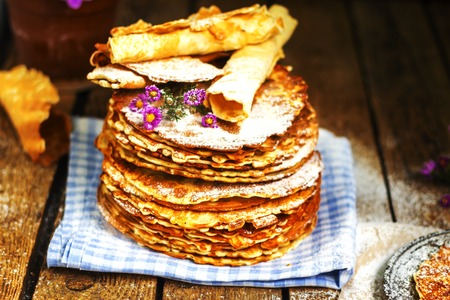 russian food: Pile of rustic homemade wafers with paper, flowers and waffle-iron on the old wooden background. Russian food. East european food