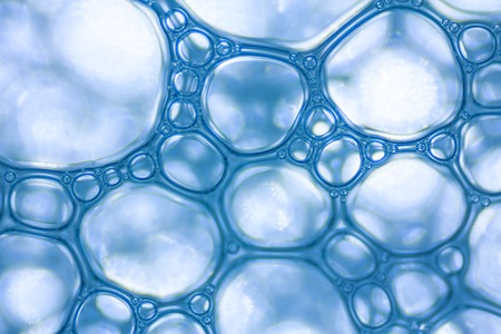 매크로보기 흰색 비누 거품 거품. 비눗물과 샤워 텍스처. 파란색 배경입니다. 소프트 포커스