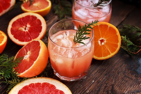 Cocktail with slices of grapefruit and orange and ice on a old rustik table background. Grapefruit Martini . Stock Photo