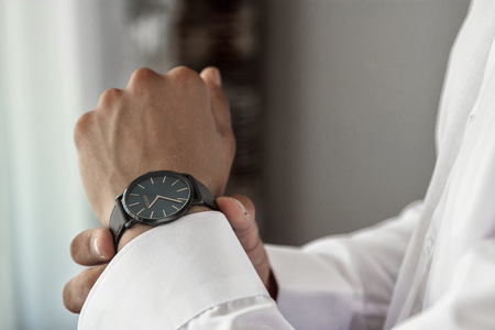 Male hands on a background of a white shirt, sleeve shirt with cufflinks and watches
