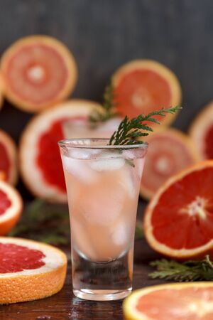 Fresh alcoholic cocktail with grapefruit and citrus, ice and juice, drink glass on a wooden board, selective focus 스톡 콘텐츠
