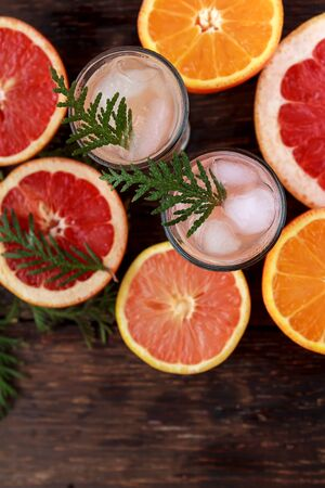 Alcoholic cocktail with grapefruit and citrus, ice and juice, drink glass on a wooden board, old rustic style.