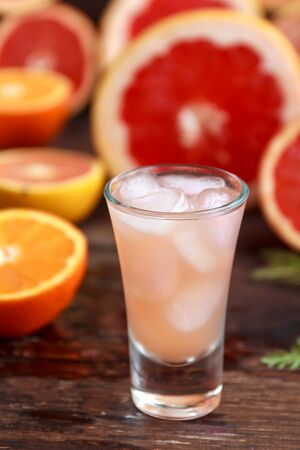 fresh grapefruits sliced and a tall glass filled with juice and vodka with ice