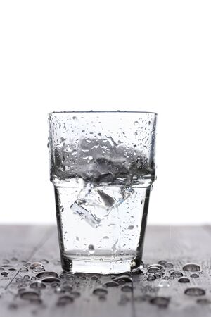 Splashing of water with ice in glass, on white 스톡 콘텐츠