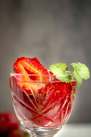 Fresh strawberry cocktail with min and ice on gray background. Space for text. Top view