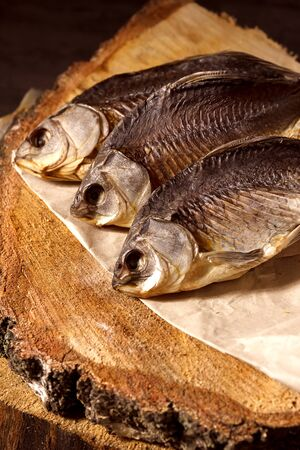 Salty dry river fish on a wooden impressive background.