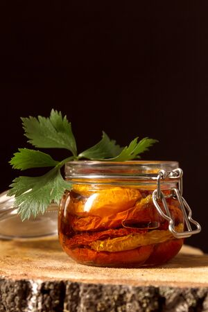 Sun-dried tomatoes with olive oil in a jar and celery on wooden background. Step by step cooking