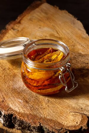 Sun-dried tomatoes with olive oil in a jar on wooden background. Step by step cooking 스톡 콘텐츠
