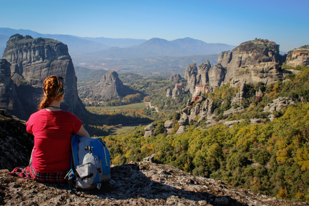 A traveler girl in a red T-shirt and a blue backpack sits high against the rocks of the Meteora temple complex in Greece on a bright summer sunny day.