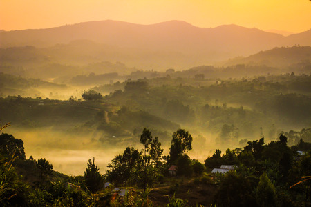 Gentle yellow light and light mist over the hills in country side with traditional houses and the tropical nature of Uganda on the border with the Congo at dawn