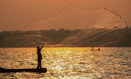 Fischer wirft ein Netz im Viktoriasee aus. Uganda