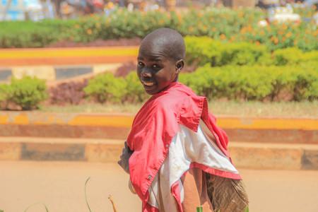 Kampala, Uganda - January 22, 2018: A local boy walks down Kampala street, turns around and smiles