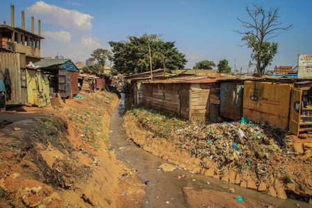 Kampala, Uganda - January 22, 2015: A very dirty river with rubbish and mountains of plastic on the banks among poor houses in slums.