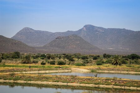 Marsabit, Kenya - January 16, 2015: African fields flooded with water, palm trees and mountains