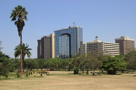 Nairobi, Kenya - January 17, 2015: central city park with palm trees and business center view