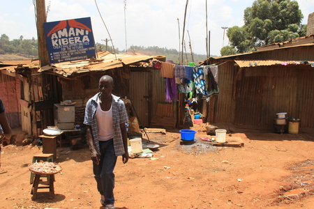 Kibera, Nairobi, Kenya - February 13, 2015: African poor man walks down the street near the huts