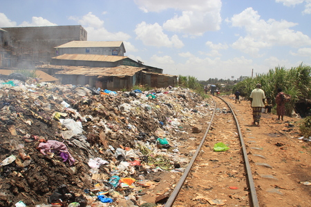 Kibera, Nairobi, Kenya - February 13, 2015: a huge mountain of garbage and a railway in the poorest area of Nairobi - Kibera