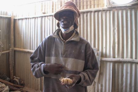 Kibera, Nairobi, Kenya - February 13, 2015: African young male worker at a souvenir factory in Nairobis poorest district - Kibera Editorial