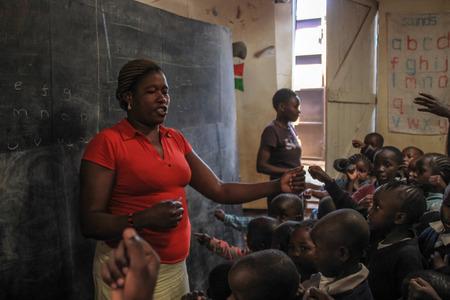 Kibera, Nairobi, Kenya - February 13, 2015: African volunteer teacher in the poorest school in Kibera