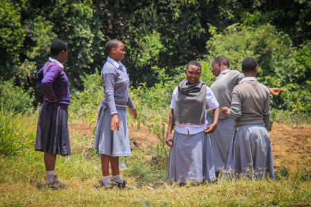 Arusha, Tanzania - March 13, 2015: Tanzanian public high school students work in the school yard Editorial