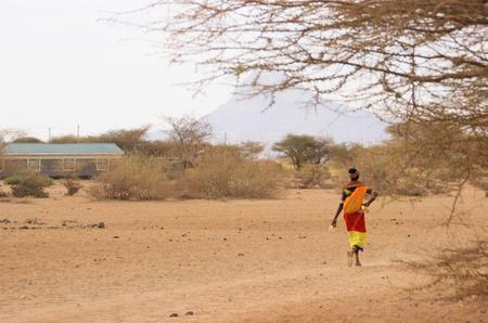 Marsabit, Kenya - January 16, 2015: African woman from the Samburu tribe (related to the Masai tribe) in national costume walks on savanna