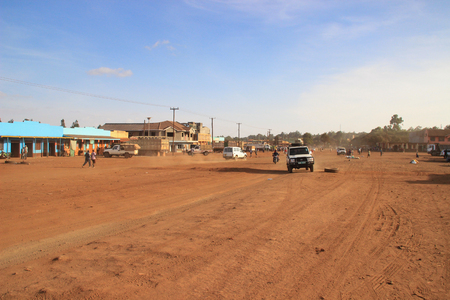 Marsabit, Kenya - January 16, 2015: a city street with an orange-covered road, shops and a car