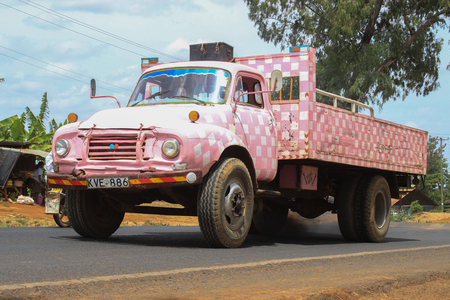 Nairobi, Kenya - February 17, 2015: funny and unusual pink glamorous checkered truck transporting goods on the road. Vintage pink truck in Africa