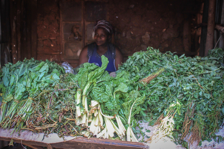 Kibera, Nairobi, Kenya - February 13, 2015: African woman selling greens on the counter in one of the poorest cities in Africa Editorial