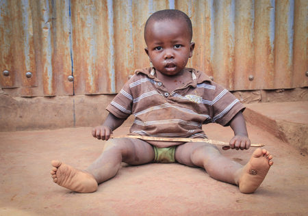 Kibera, Nairobi, Kenya - February 13, 2015: a small dirty black child sits on the floor in the slums and holds a stick in his hands Editorial