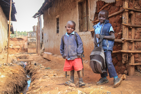 Kibera, Nairobi, Kenya - February 13, 2015: Two poor black boys in slums go to school in a poor district of Kibera.
