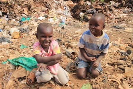 Kibera, Nairobi, Kenya - February 13, 2015: Two poor black boys in the slums of Kibera playing on the trash Editorial