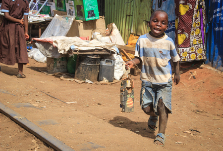Kibera, Nairobi, Kenya - February 13, 2015: a poor black boy from the slums of Kibera playing with trash