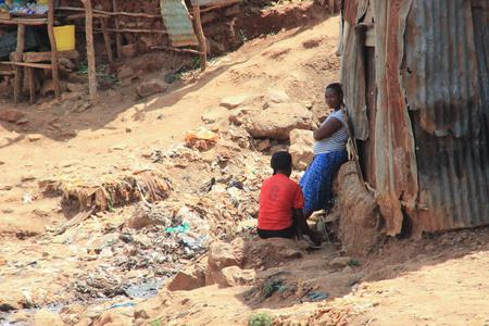 Kibera, Nairobi, Kenya - February 13, 2015: two African women near the huts are talking among the garbage