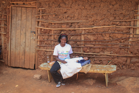 Kibera, Nairobi, Kenya - February 13, 2015: African woman in a white T-shirt holding a baby in her arms and sitting on a bench near a clay hut