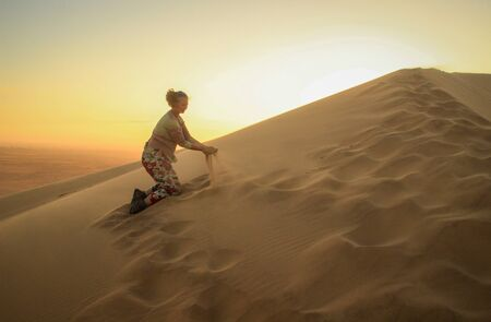 The highest sand dunes in the world at sunset in Namib Desert, in the Namib-Nacluft National Park in Namibia. Sossusvlei. Young woman tourist playing with sand